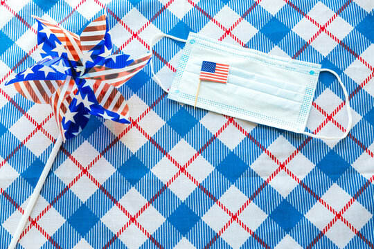 July 4 background. USA flags, sunglasses and medical mask on blue tablecloth. Independence Day of America during coronavirus covid-19 pandemic quarantine. Flat lay, top view, daylight. Copy space text