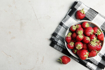 Fototapete - Delicious ripe strawberries in bowl on light grey table, flat lay. Space for text
