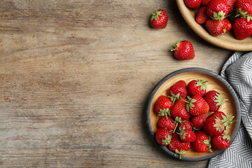 Fototapete - Delicious ripe strawberries on wooden table, flat lay. Space for text
