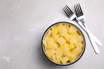 Fototapete - Tasty canned pineapple pieces and forks on light grey marble table, flat lay. Space for text