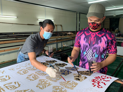 Malaysian textile and fashion designer Mohd Hafiz Drahman (R) and his worker paint customised masks using batik, a traditional Malay design technique at a studio, amid the coronavirus disease (COVID-19) outbreak in Shah Alam