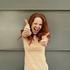 Exuberant young woman giving a double thumbs up