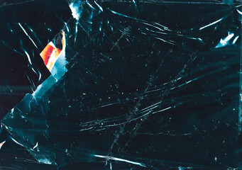 Cracked glass background. Fractured ice texture. Teal blue scratched surface with dust orange glow.