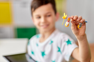 childhood, imagination and dream concept - close up of happy little boy playing with airplane toy...