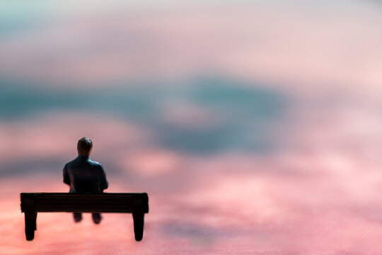 Miniature figurine posed as man sitting alone on a bench in surreal scenery, minimalist abstract concept image
