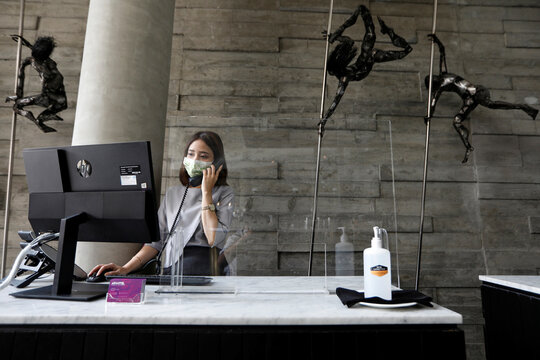 A receptionist staff wearing a protective mask uses a phone at the lobby of Artotel Thamrin, following the coronavirus disease (COVID-19) outbreak, in Jakarta