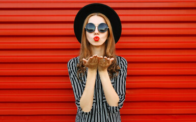Fashion portrait young woman blowing red lips sending sweet air kiss over red wall background