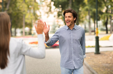 Man Waving Hello Gesture Meeting Female Friend Walking Outdoors