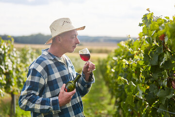 Winegrower in the vineyard with glass of red wine