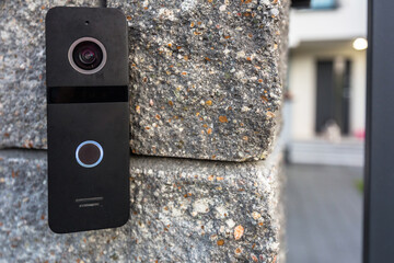Outdoor video intercom system with speaker mounted on the stone wall
