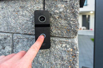 Hand pressing button of video intercom mounted on the stone wall