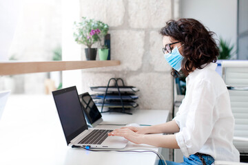 Worker wearing protective mask in safe office. Protection employees on workplace at hotel...