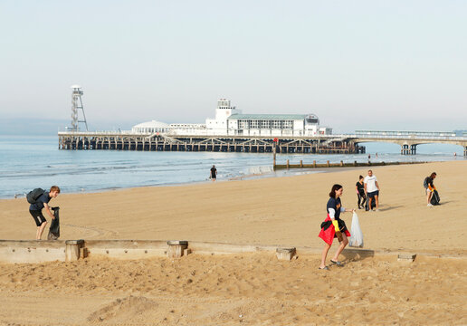 People pick up litter left on Bournemouth beach, as the outbreak of the coronavirus disease (COVID-19) continues in Bournemouth
