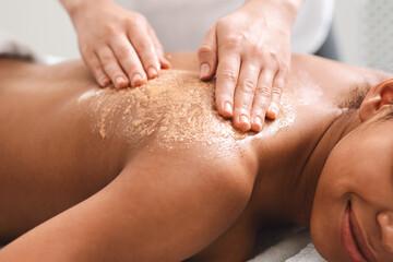 Closeup of black girl having skin peeling massage at spa