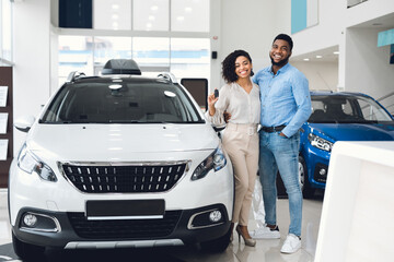 Joyful Couple Showing New Auto Key Standing In Dealership Center