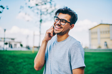 Cheerful hipster blogger in optical spectacles laughing while talking with best friend on...