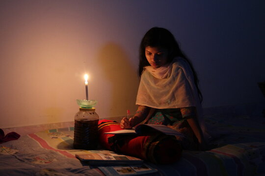A young girl studying at home with candlelight after electricity load shedding at Dhaka City, Bnagladesh. Blackout. Electricity Problem.