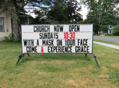 "Funny rhyming church sign says ""With a mask on your face, come and experience grace"" as churches reopen for services, with social distancing protocols to protect the congregation, after Covid"