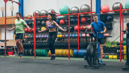 Group of athletes doing air bike and skipping rope at the gym