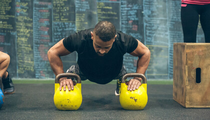 Sportsman doing push-ups with kettlebells in the gym