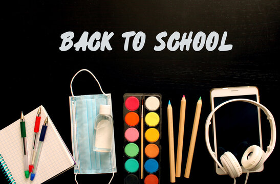 Back to school and protection against coronavirus and other infections. Top view of school stationery, medical mask, antiseptic, electronic tablet and headphones on a background of black wooden table