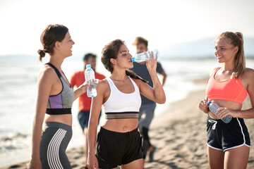 Young fitness womans drinking water by the sea.