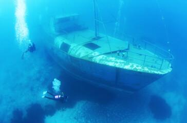 Fotobehang Schipbreuk Scuba Divers Exploring underwater ship wreck