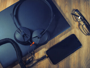 Flat lay top view, of a wooden office desk with a laptop, smartphone and headphones. Streaming music from the internet