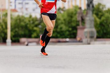 Fotomurales - man runner in black compression socks running city marathon