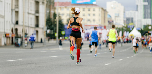 Wall Mural - back young girl runner in compression socks and kinesio tape on thigh run marathon