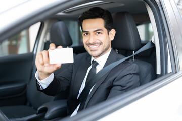Businessman Showing Identity Card In Car