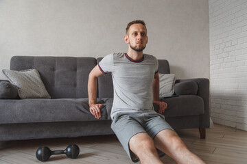 Young caucasian guy working out at home with sofa. Man doing physical excercises at home. Home work out fitness.