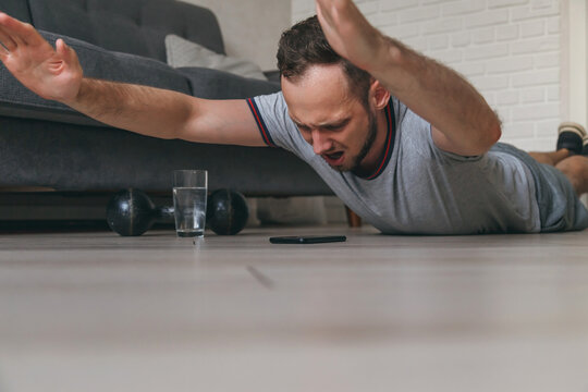 Fit young caucasian man doing superman's exercise at home, training in living room