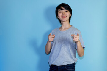 Pointing asian young adult man with copy space