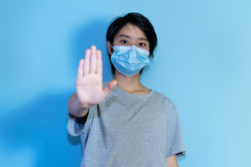 Asian young adult man wearing protection mask and gesturing stop