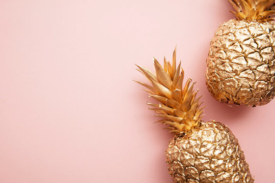 Gold tropical pineapple on a pastel pink background. Flat lay summer background