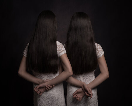 Twin sisters with black long hair and white dress with arms and hands resting on back seen from behind in dark painterly studio style
