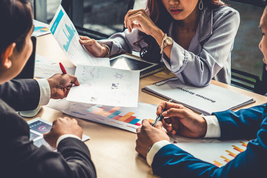 Smart businessman and businesswoman talking discussion in group meeting at office table in a modern office interior. Business collaboration strategic planning and brainstorming of coworkers.