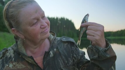 Wall Mural - Woman fishing. Portrait of the eldery woman angler holding tiny fish in her hand. Woman fishing on the summer picturesque lake during calm evening