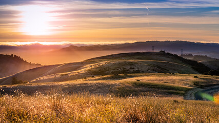 Landscape in Santa Cruz mountains, with sun rays illuminating hills covered in dry grass; People...