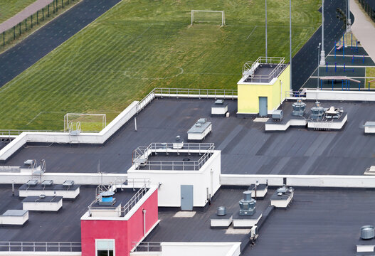 Drone point of view dark flat roof with air conditioners and hydro insulation membranes on top of a modern apartment building with green sport field residential area.