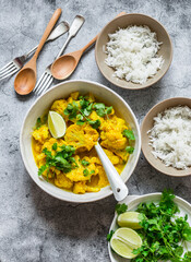 Indian food lunch table - vegetarian cauliflower curry sauce, rice, cilantro, lime on grey background, top view