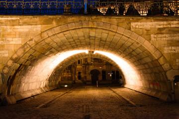 Tunnel under the bridge illuminated at night
