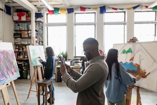 Man photographing artwork on phone in studio