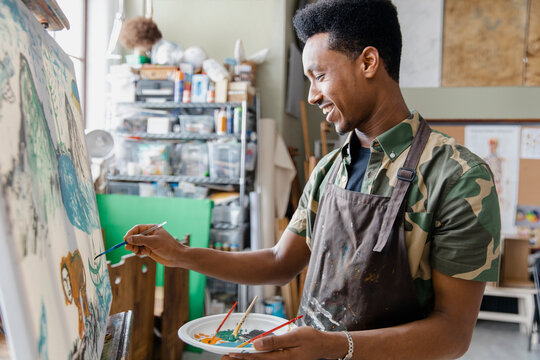 Young man painting in art studio