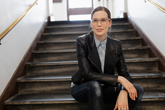 Mature woman in leather jacket sitting on stairs