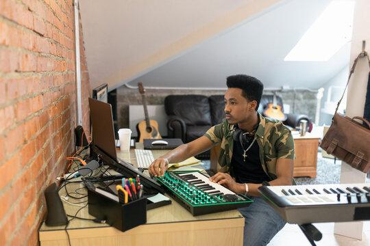 Young man using keyboard in music studio