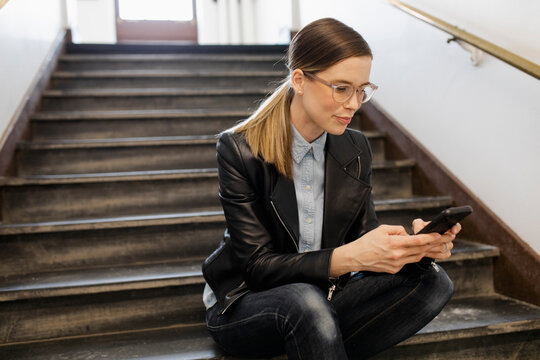 Mature woman sitting on stairs using phone