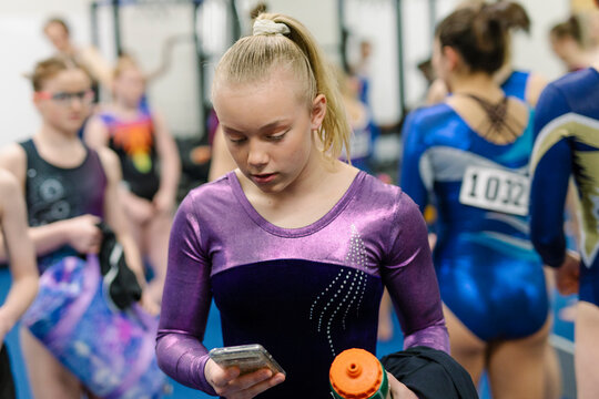 Female gymnast using phone backstage