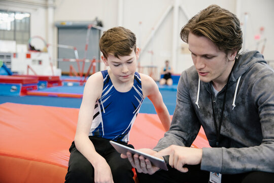 Gym coach using tablet and talking to boy